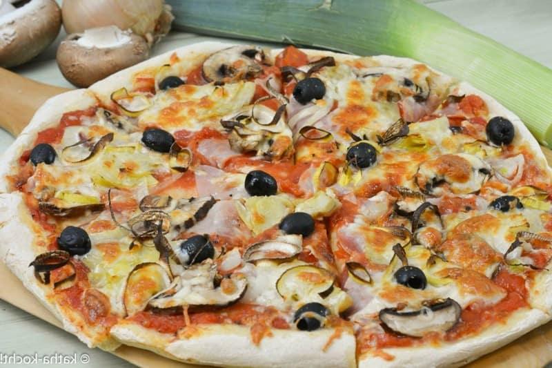 Pizza Parma mit Schinken, Mozzarella, Tomaten und schwarzen Oliven