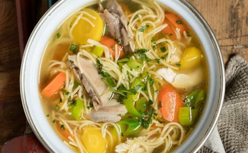 Sommerliche Suppe mit Hähnchen, Nudeln, viel Gemüse und Kräutern