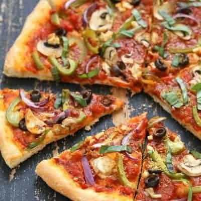 Vegane Pizza mit Gemüse, Pilzen und Oliven