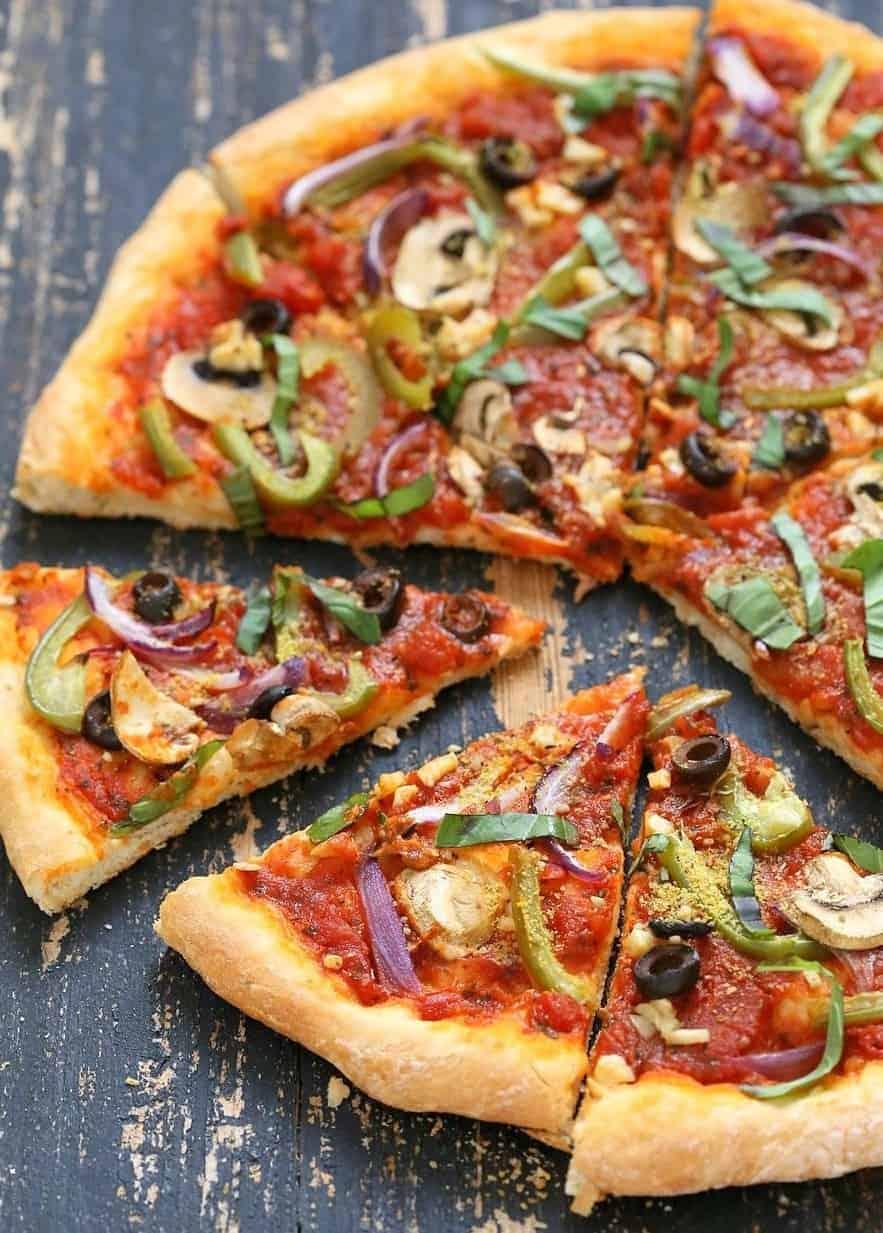 Vegane Pizza mit viel Gemüse, Pilzen und Kalamata