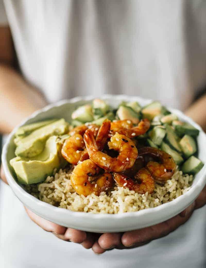 Gesunde Buddha Bowl mit Reis, Gurke, Avocado und Garnelen